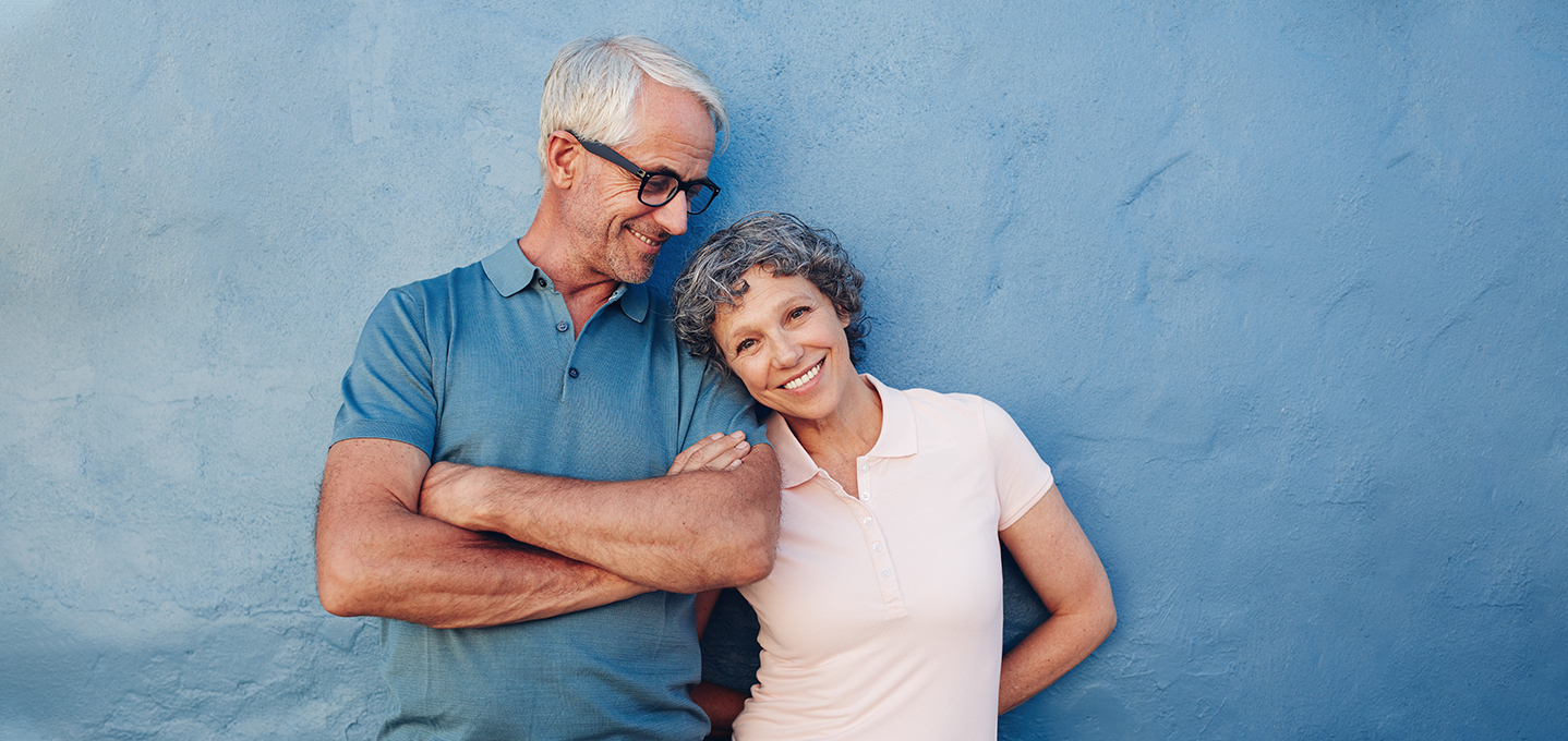 Image description: a mature couple leaning against a blue textured wall smiling.