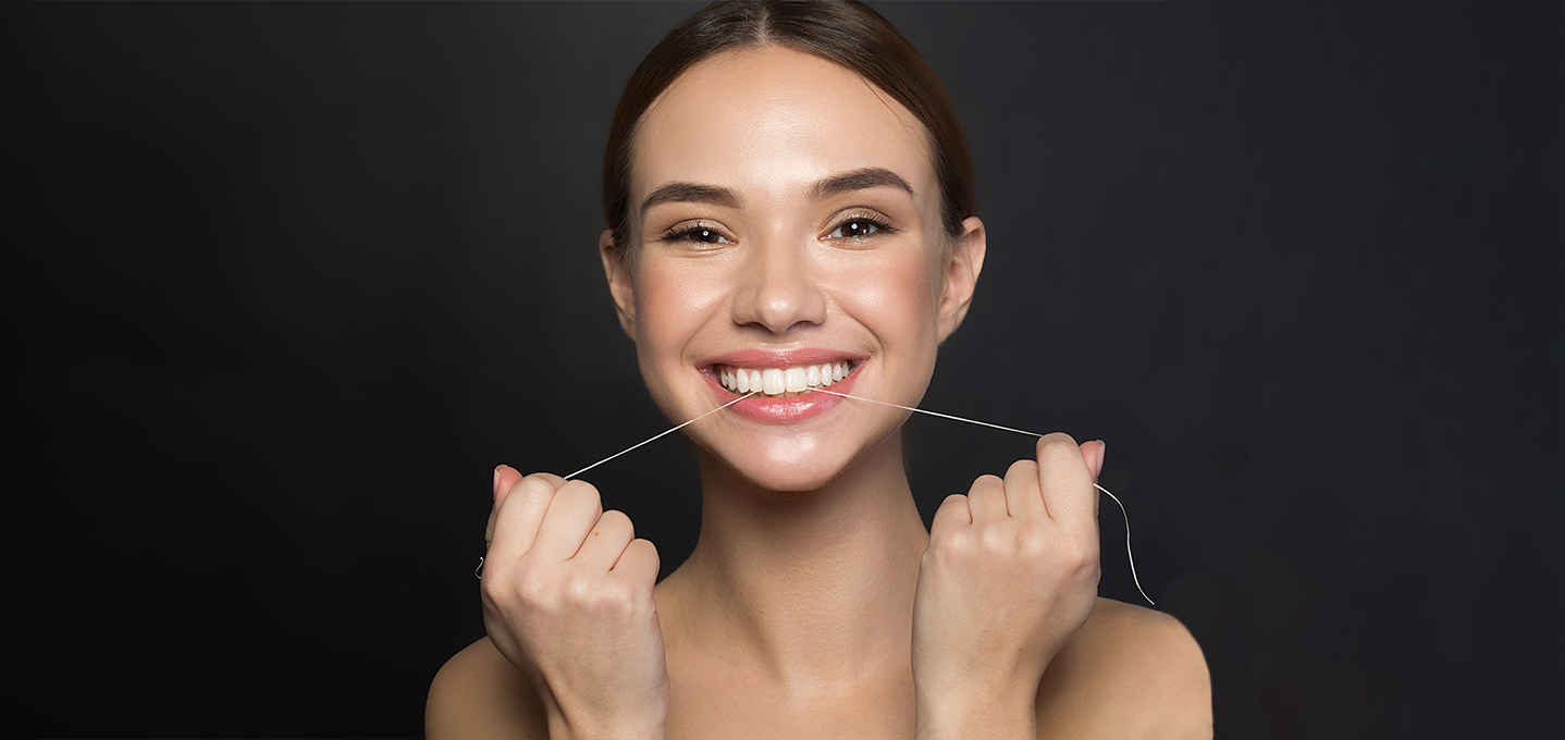 Image description: a young lady smiling and pretending to floss her teeth.