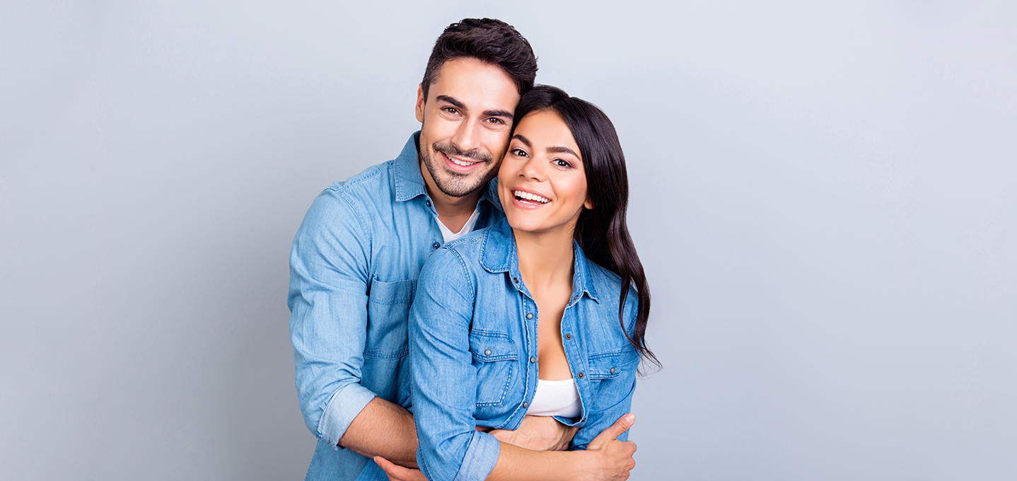 Image description: a young couple embracing and smiling.