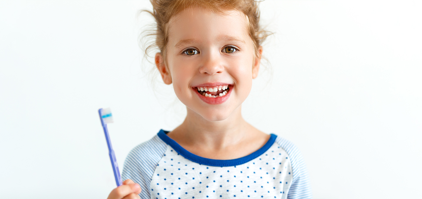 Image description: little girl who has recently lost her front two teeth smiling and holding a toothbrush.