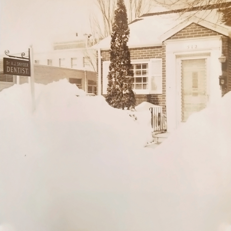 Image description: the original dental office of Dr. Snyder in Willmar, Minnesota with large snow drifts in front.